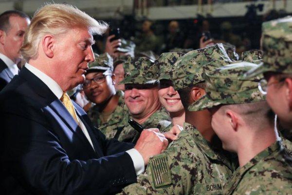 Presiden AS Donald Trump menandatangani selembar uang milik seorang tentara AS ketika dia berkunjung ke markas militer AS di Yokosuka, Tokyo, Jepang, Selasa (28/5/2019). - Reuters/Jonathan Ernst