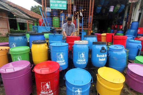 Perajin merapikan tempat sampah hasil daur ulang - ANTARA