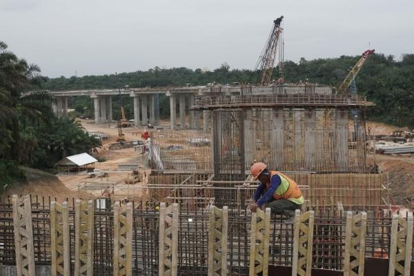 Pekerja menyelesaikan pembangunan Jembatan Simpang Perawang yang menjadi akses menuju Tol Pekanbaru-Dumai (Pekdum) di Riau, Sabtu (23/11/2019). - Bisnis/Himawan L. Nugraha