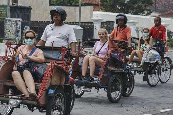 Wisatawan mancanegara menggunakan jasa becak motor di kawasan Titik Nol Kilometer, DI Yogyakarta, Jumat (28/7). - ANTARA/Hendra Nurdiyansyah