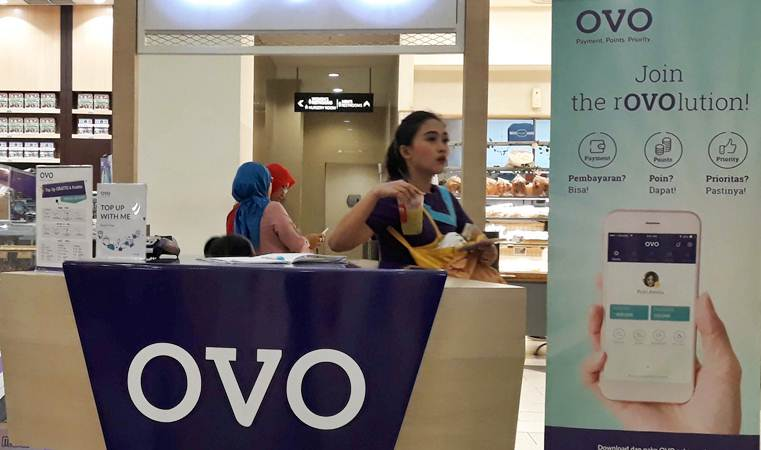 Karyawan melintas di gerai transaksi pembayaran digital OVO, di Jakarta, Senin (25/3/2019). - Bisnis/Endang Muchtar