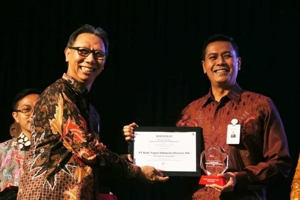 Direktur Bisnis Konsumer BNI Anggoro Eko Cahyo (kanan) menerima penghargaan Pariwara Jasa Keuangan Terbaik 2019 dari Anggota Dewan Komisioner Bidang Edukasi dan Perlindungan Konsumen OJK Tirta Segara (kiri) di Jakarta, Kamis (5/12 - 2019). /Istimewa