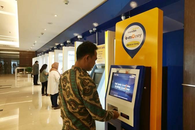 Nasabah melakukan transaksi top-up saldo e-money melalui mesin khusus e-money di salah satu cabang Bank Mandiri, di Jakarta, Senin (10/6/2019). - Bisnis/Nurul Hidayat