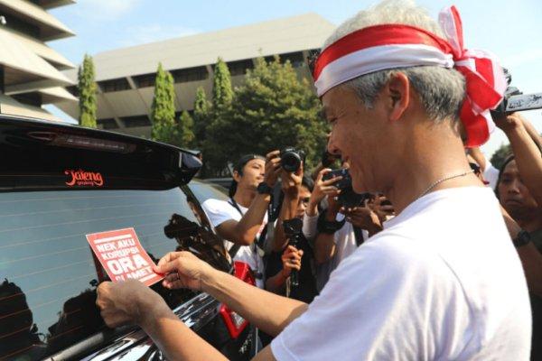 Gubernur Jawa Tengah Ganjar Pranowo bersama ribuan pelajar menempelkan stiker bertuliskan Nek Aku Korupsi, Aku Ora Slamet di mobil-mobil dinas PNS yang parkir di halaman Kantor Pemerintah Provinsi Jawa Tengah, Minggu (8/12 - 2019). Istimewa)