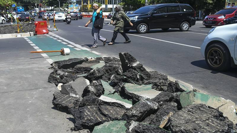 Warga melintas di samping jalur sepeda yang dibongkar di kawasan Cikini, Jakarta, Selasa (19/11/2019). Pemprov DKI Jakarta membongkar jalur sepeda yang baru diresmikan tersebut untuk perlebaran trotoar. - Antara