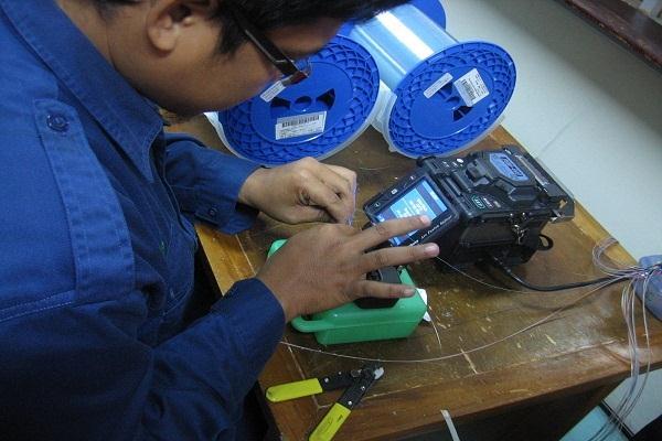 Seorang pekerja menyambung kabel serat optik di sebuah pabrik kabel. - Bisnis.com
