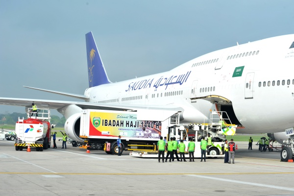 Sejumlah petugas melakukan proses refuelling avtur ke pesawat Boeing 747 milik Saudi Arabia yang akan menerbangkan 450 calon jemaah haji di Bandara Sultan Mahmud Badaruddin II Palembang, Sumsel, Rabu (10/7/2019). - ANTARA FOTO/Feny Selly
