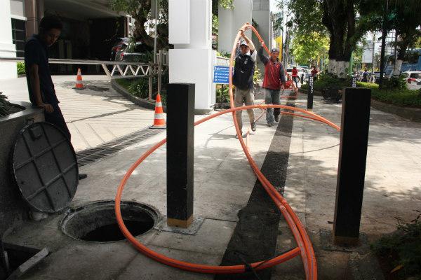Sejumlah pekerja memasang selang pelindung kabel fiber optik ke dalam saluran bawah tanah pada proyek revitalisasi trotoar jalan Jenderal Sudirman, Jogja, Senin (9/12/2019). - Harian Jogja/Desi Suryanto
