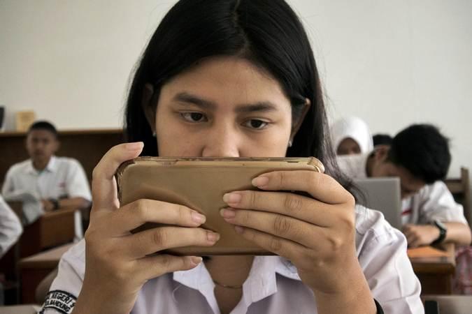 Seorang pelajar di sebuah SMA Negeri Kota Bandung, Jawa Barat, Senin (18/3/2019), tengah menggunakan smartphone. - ANTARA FOTO/Novrian Arbi