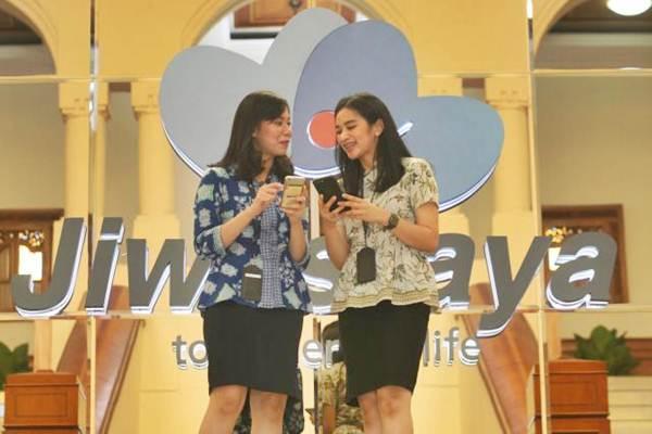 Karyawati berbincang di dekat logo PT Asuransi Jiwasraya di Jakarta, Jumat (14/9/2018). - JIBI/Dedi Gunawan