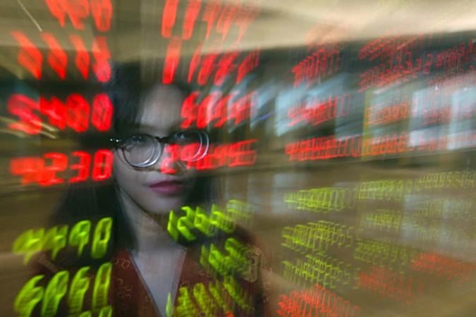 Karyawan berada di depan papan elektronik yang menampilkan harga saham. - Bisnis/Abdullah Azzam