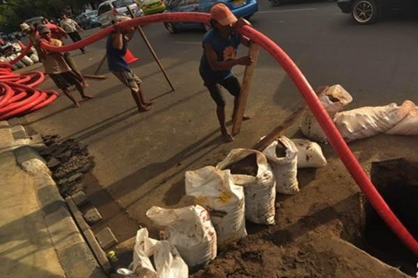 Sejumlah pekerja memasang kabel optik saluran listrik di jalan Gajah Mada, Jakarta - Antara