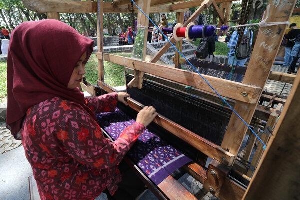 Perajin memperagakan cara membuat kain tenun ikat khas Kediri saat Dhoho Street Fashion di Taman Hutan Joyoboyo, Kota Kediri, Jawa Timur, Kamis (5/12/2019). - Antara/Prasetia Fauzani