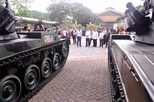 Presiden Joko Widodo (tengah) saat melihat-lihat tank produksi PT Pindad di Divisi Senjata PT Pindad, Bandung, Jawa Barat, Senin (12/1). Presiden mendorong berkembangnya industri alustista produksi dalam negeri guna memenuhi kebutuhan pertahanan nasional. - ANTARA