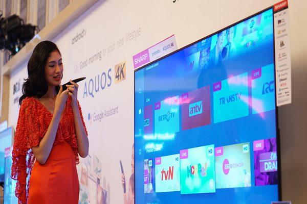Seorang model memperagakan perintah suara menggunakan remote untuk menjalankan SHARP Android TV dengan Google Assistant - Istimewa