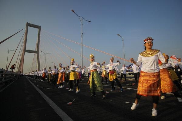 Peserta membawakan Tari Sajojo saat memperingati Hari Ibu di bentang tengah Jembatan Suramadu, Surabaya, Jawa Timur, Sabtu (7/12/2019). - Antara/Moch Asim