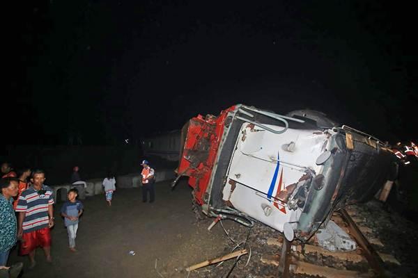Petugas melakukan evakuasi pada gerbong kereta api Sancaka jurusan Yogyakarta-Surabaya yang terguling usai terlibat kecelakaan dengan truk pengangkut bantalan rel di perlintasan KM 215 Walikukun, Ngawi, Jawa Timur, Jumat (6/4/2018). - ANTARA/Eric S