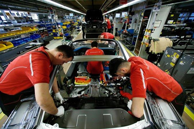 Karyawan produsen mobil Jerman Porsche mengerjakan Porsche 911 di pabrik Porsche di Stuttgart-Zuffenhausen, Jerman, 19 Februari 2019. - Reuters/Ralph Orlowski