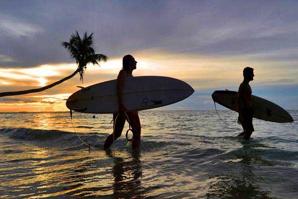 Siluet wisatawan mancanegara membawa papan surfing (selancar) di Pantai Mapadegat, Kepulauan Mentawai, Sumatra Barat. - Antara/Iggoy el Fitra