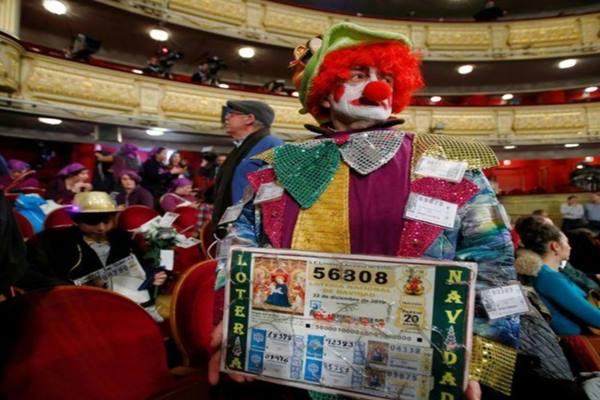 Seseorang mempeihatkan fotokopi tiket undian El Gordo, saat menghadiri undian lotre Spanyol tersebut. - Reuters