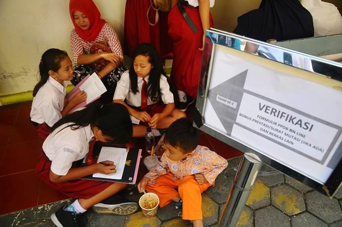 Sejumlah siswa dan orang tua murid antre untuk mengikuti seleksi Penerimaan Peserta Didik Baru (PPDB) ) jalur zonasi, di SMP 1 Kudus, Jawa Tengah, Rabu (19/6/2019). - ANTARA/Yusuf Nugroho