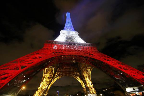 Menara Eiffel disinari lampur berwarna putih, merah dan biru sesuai warna bendera Prancis sebagai penghormatan kepada korban tewas serangan teroris di Paris, Jumat (13/11/2015) - Reuters