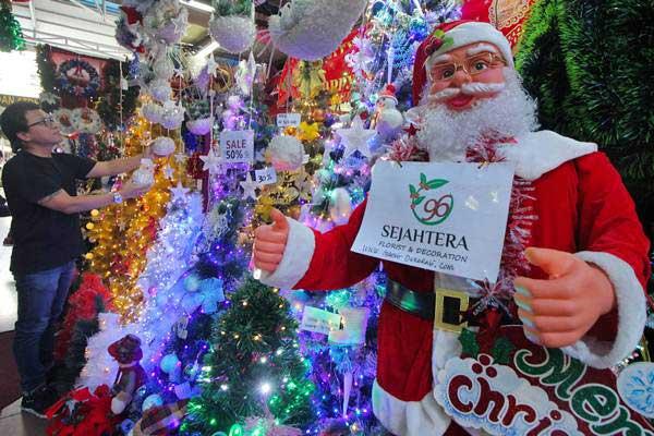 Penjual menata aksesoris Natal di stannya di salah satu pusat perbelanjaan di Surabaya, Jawa Timur, Jumat (14/12/2018). - ANTARA/Didik Suhartono