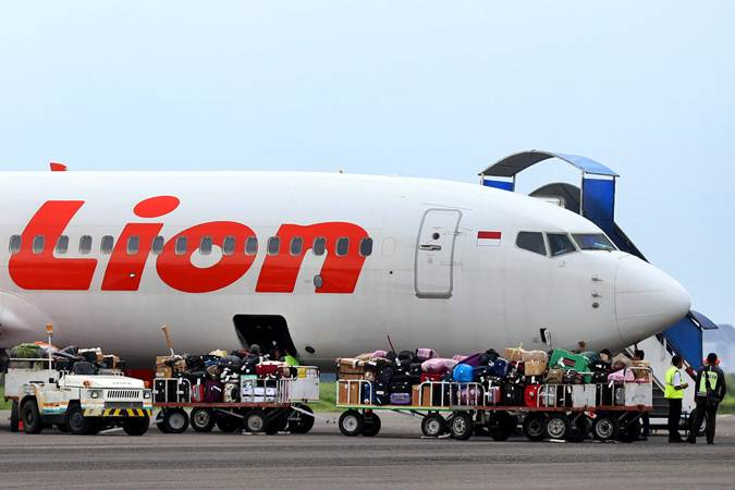 Pekerja melakukan bongkar muat bagasi penumpang pesawat Lion Air, di Bandara Husein Sastranegara Bandung, Jawa Barat. - Bisnis/Rachman