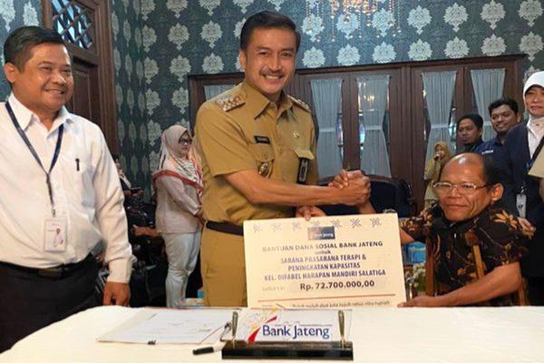 Wali Kota Salatiga Yuliyanto (tengah) didampingi Pimpinan Bank Jateng Cabang Salatiga Yohanes Suhartono (kiri) menyerahkan bantuan simbolis dari Bank Jateng  kepada ketua  kelompok difabel Harapan Mandiri  Ngatimin di Rumah Dinas Wali Kota, Senin (23 - 12).