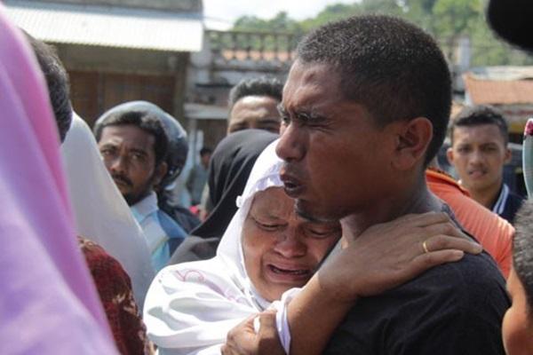 Keluarga korban gempa menangis saat menunggu evakuasi saudaranya yang tertimpa reruntuhan bangunan di Pasar Tringgadeng, Pidie Jaya, Aceh, Rabu (7/12/2016).  - Antara
