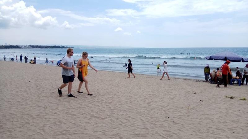 Wisatawan berjalan di pantai Kuta, Bali, Selasa (31/12/2019). Sejak pagi hingga siang tadi. Diperkirakan ada 5.000 orang lebih yang akan memadati Pantai favorit untuk menghabiskan pergantian tahun di pulau dewata tersebut. - Bisnis/Busrah Ardans