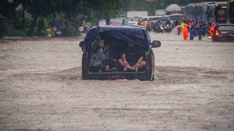 Warga menaiki mobil saat melintasi genangan banjir di Jalan DI Panjaitan, Cawang, Rabu (1/1/2020). Banjir tersebut disebabkan karena tingginya intensitas hujan yang mengguyur sejak Selasa (31/12/2019).  - ANTARA /Aprillio Akbar