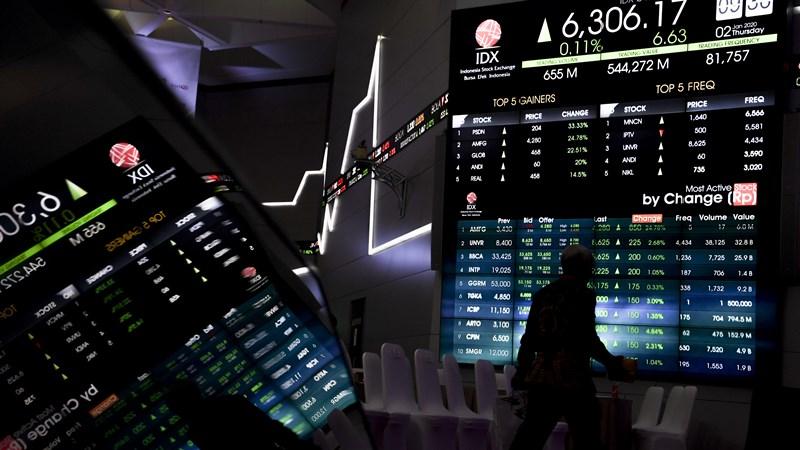 Pekerja berjalan di dekat monitor pergerakan bursa saham saat pembukaan perdagangan saham tahun 2020 di gedung Bursa Efek Indonesia, Jakarta, Kamis (2/1/2020). - ANTARA FOTO/Hafidz Mubarak A