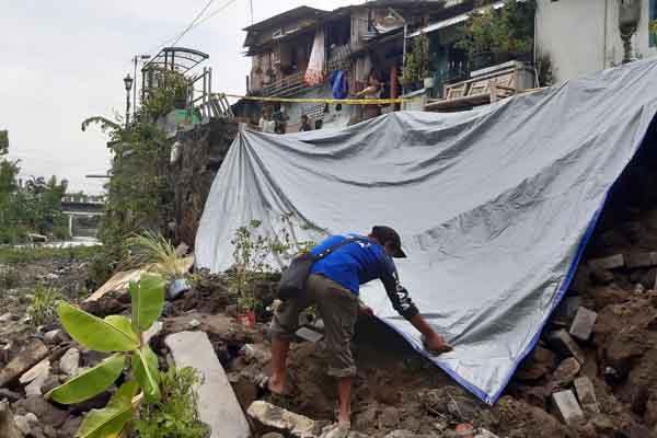 Tim Tagana menutup talud dengan terpal di Kampung Serangan, Notoprajan, Ngampilan, Sabtu (4/1/2020). - Harian Jogja/Lugas Subarkah