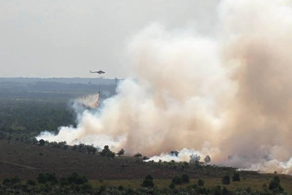 Helikopter BNPB jenis MI-8 melakukan pengeboman air di atas areal hutan dan lahan yang terbakar di Desa Medang Kampai, Dumai, Riau, Selasa (9/8). - Antara