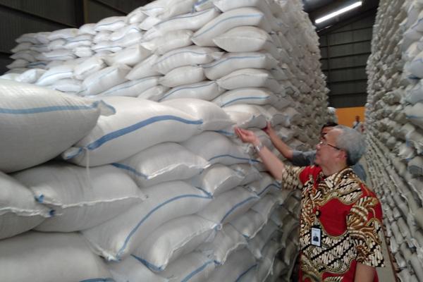 Pemimpin Wilayah Perum Bulog Jawa Tengah Basirun (mengenakan batik) saat mengecek beras di Gudang Bulog Sumberejo, Kaliwungu, Kabupaten Kendal pada Jumat 20 Desember 2019. - Bisnis/Alif Nazzala Rizqi