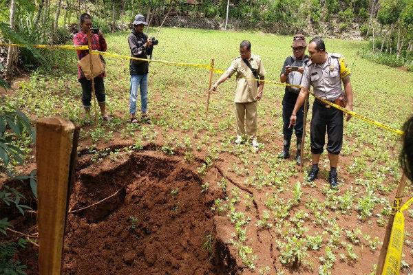 Kepala Dusun Tleseh, Desa Karangawen, Kecamatan Girisubo, Tariyo (tengah), menunjukkan fenomena sinkhole yang muncul di salah satu ladang milik warga, Selasa (7/1/2020). - Harian Jogja/David Kurniawan