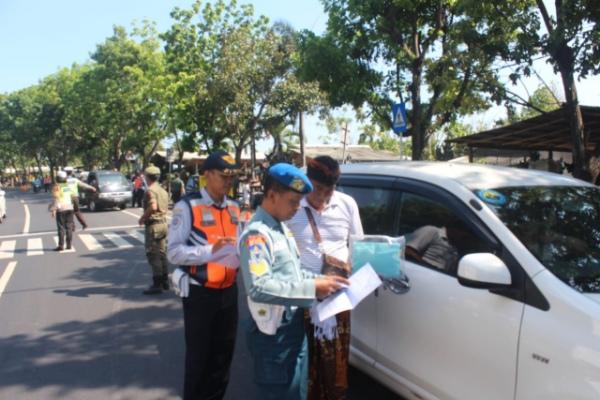 Foto: Petugas Dishub Denpasar menindak sejumlah kendaraan yang menggangu lalu lintas di Kota Denpasar. Kendaraan yang melanggar disanksi berupa penempelan stiker, penggembokan kendaraan, penggembosan dengan pencabutan pintil hingga penderekan. - Istimewa