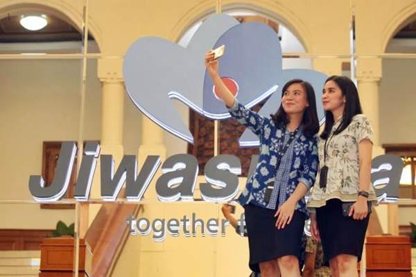 Karyawati melakukan swafoto di dekat logo PT Asuransi Jiwasraya di Jakarta, Jumat (14/9/2018). - JIBI/Dedi Gunawan