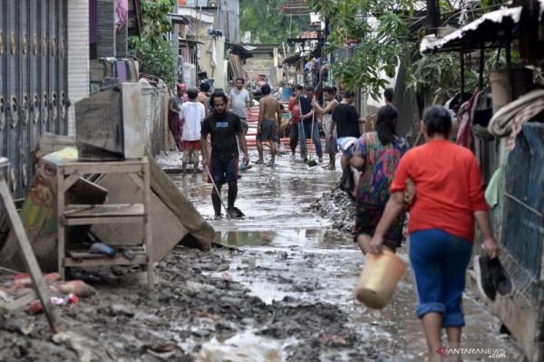 Sejumlah warga membersihkan lumpur pasca banjir yang menggenangi wilayah Jalan Mawar V RT. 008 RW 03, Kelurahan Margahayu, Bekasi Timur, Kota Bekasi, Jawa Barat, Senin (6/1/2020). - ANTARA FOTO/Suwandy