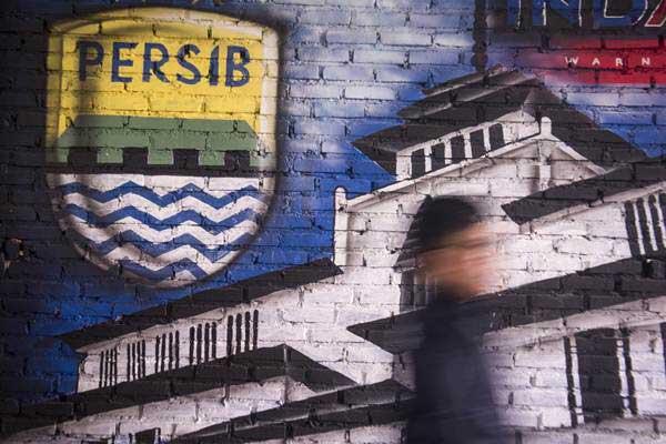 Bobotoh alias pendukung Persib berjalan di depan mural Persib di Bandung, Jawa Barat. - Antara/Novrian Arbi