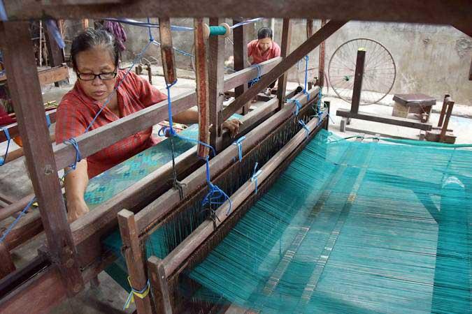 Perajin menyelesaikan pembuatan kain Endek yaitu kain khas Bali dengan menggunakan alat tenun tradisional di Denpasar, Bali - ANTARA/Nyoman Hendra Wibowo