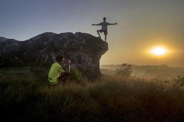 Wisatawan menikmati suasana matahari terbit dari puncak Bukit Jaddih, Bangkalan, Jawa Timur, Selasa (27/6). - Antara/Moch Asim