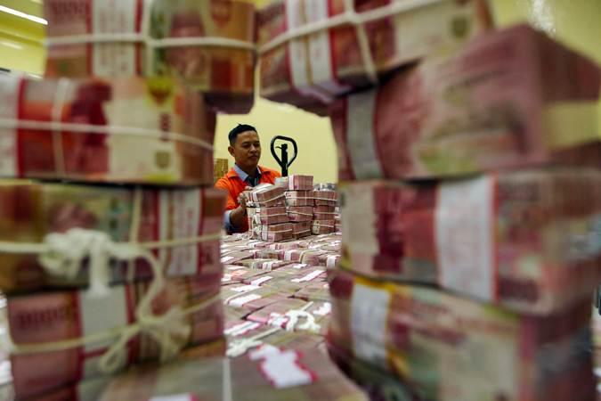 Ilustrasi karyawan menata uang rupiah. - Bisnis/Abdullah Azzam