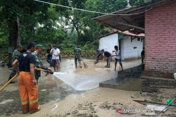 Petugas dan warga saat membersihkan lumpur yang terbawa banjir. - Antara