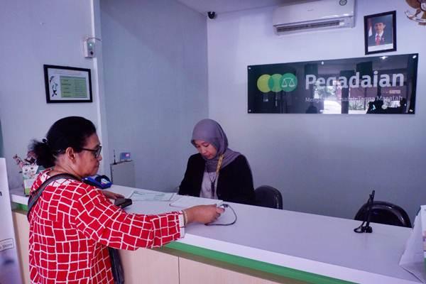 Karyawan melayani nasabah di kantor cabang Pegadaian - Bisnis/Nurul Hidayat