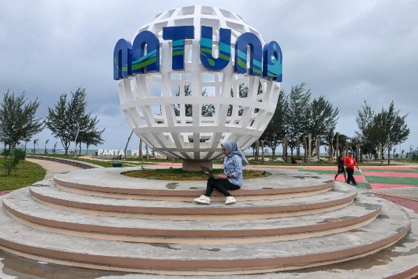 Seorang pengunjung duduk di depan tugu penunjuk Natuna di Pantai Piwang, Natuna, Kepulauan Riau, Selasa (14/1/2020). - ANTARA FOTO/M Risyal Hidayat