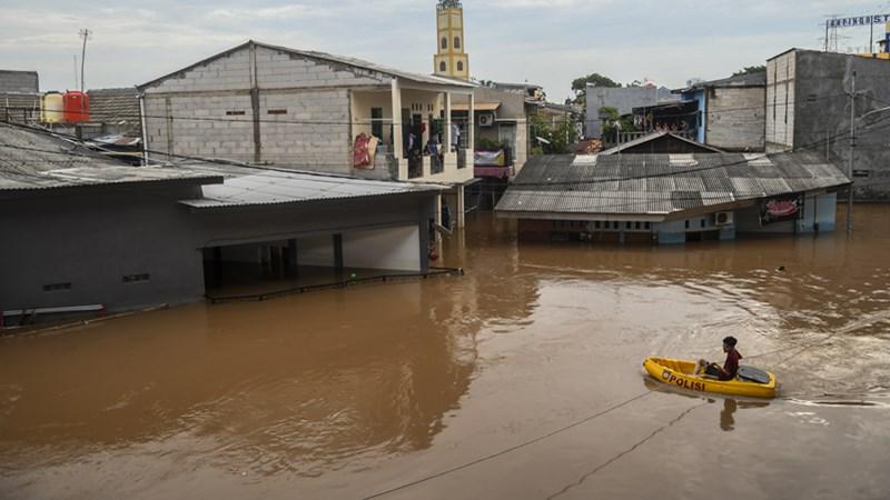 Warga melintas menggunakan perahu saat banjir di kawasan Cipinang Melayu, Jakarta, Rabu (1/1/2020). - Antara /Galih Pradipta