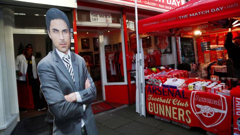 Potongan karton bergambar pelatih Arsenal Mikel Arteta tampak di bagian luar Stadion Emirates di London. - Reuters/Eddie Keogh