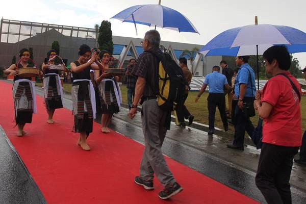 Sejumlah penari membawakan tarian Tortor saat menyambut kedatangan pertama penumpang dari Singapura setibanya di Bandara Internasional Silangit, Tapanuli, Sumatera Utara